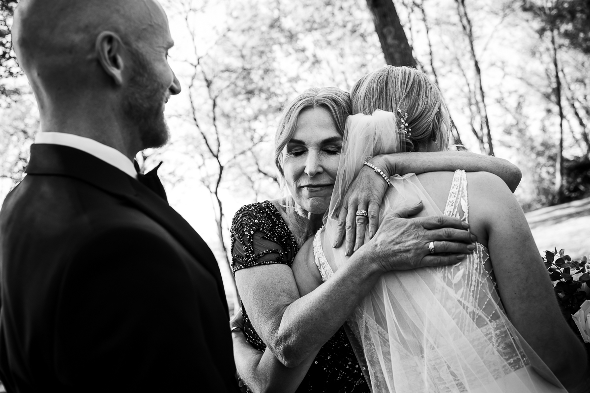mom hugging bride post ceremony in black and white while groom smiles