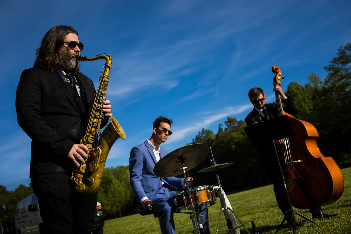 jazz trio performing outside during cocktail hour with saxophone drums and cello