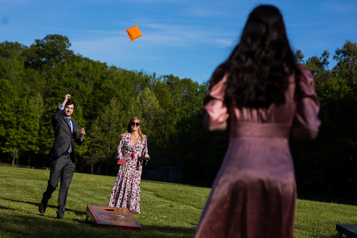 wedding guests playing outside games corn hole during cocktail hour