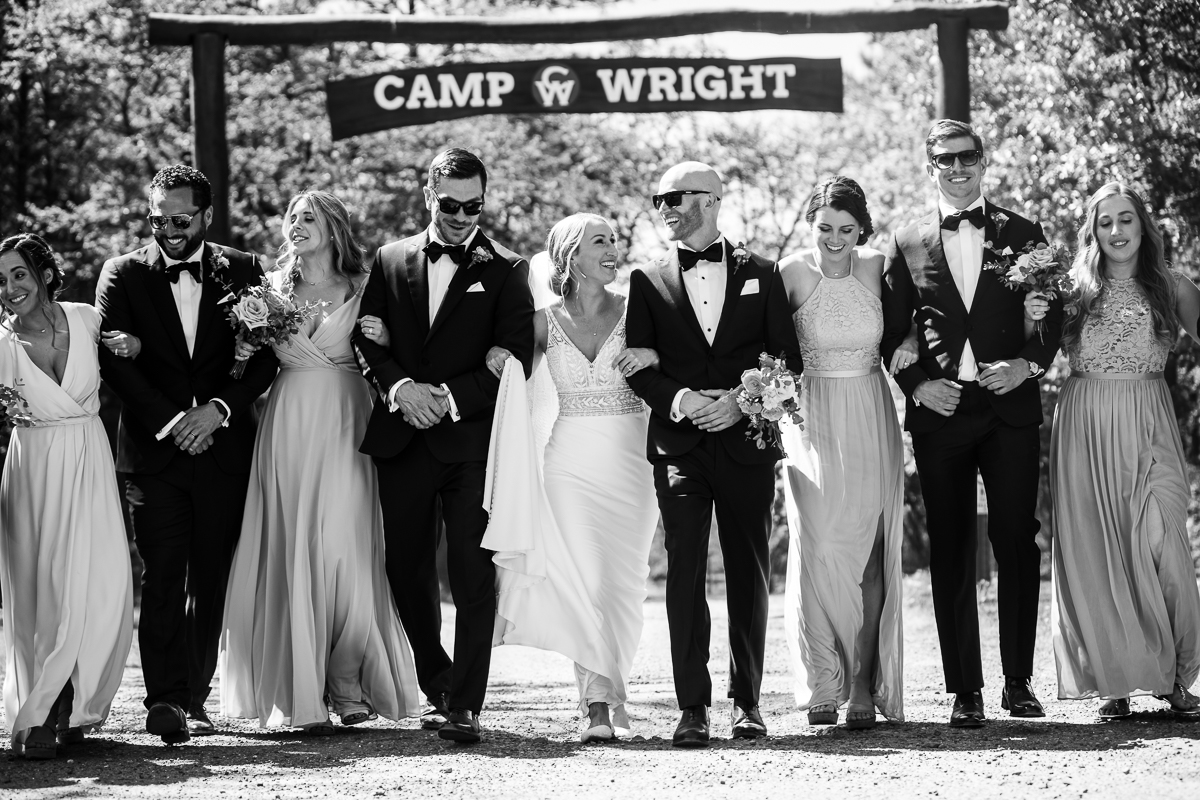 fun wedding party walking together in front of camp wright sign black and white