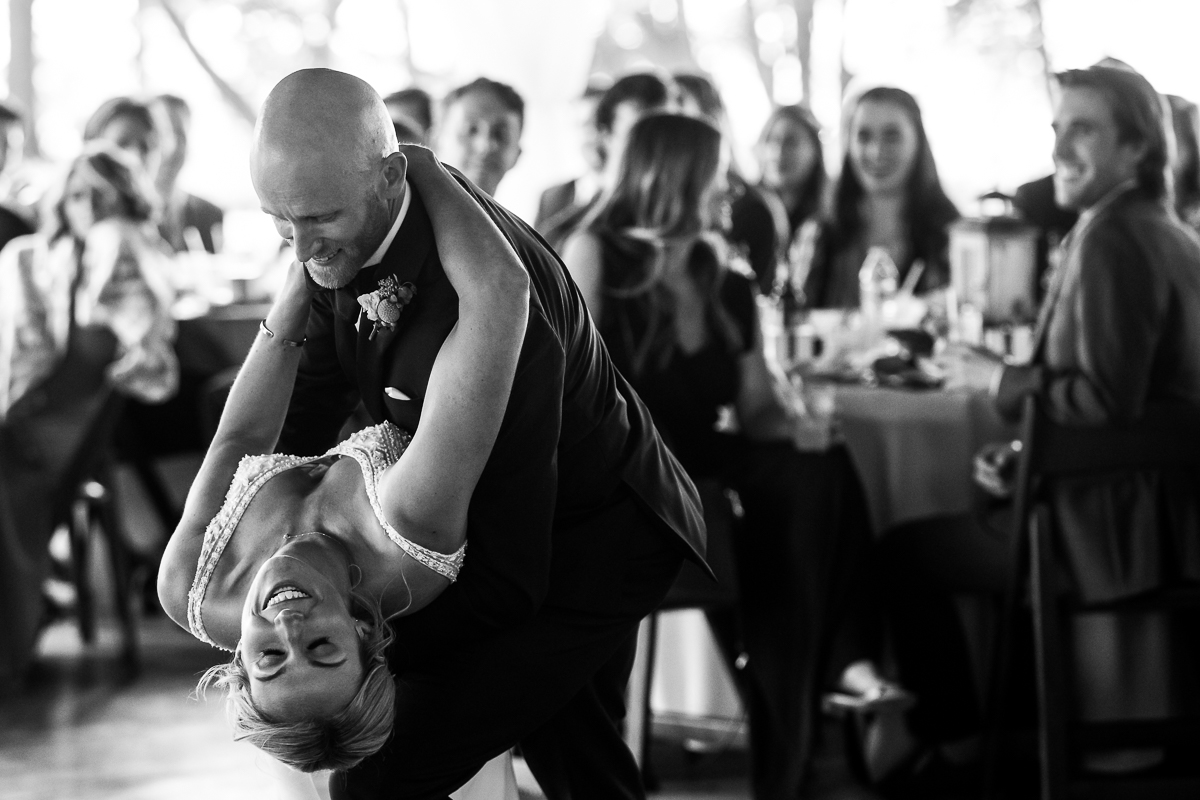 groom dipping bride during first dance in black and white