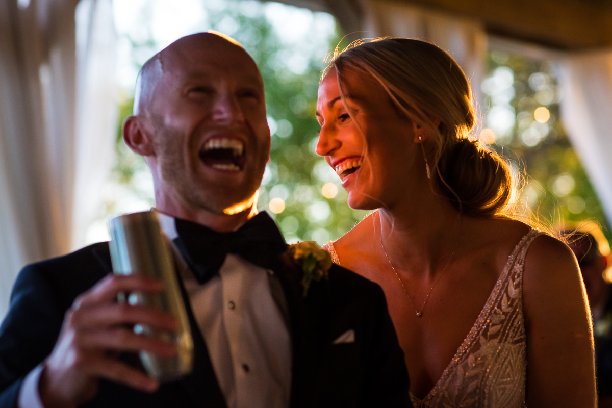 wedding couple laughing during toasts at reception under tent