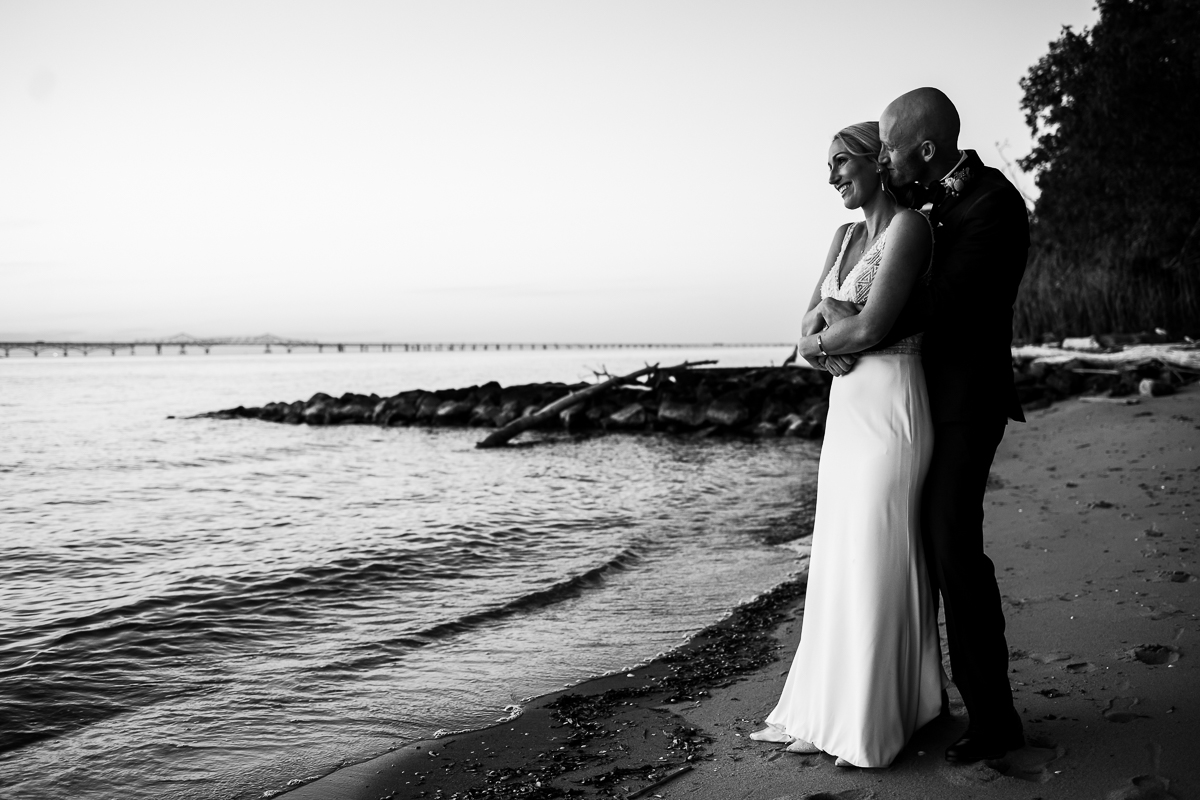black and white photo of couple standing facing Chesapeake bay with tide coming into shore in a stevensville maryland wedding