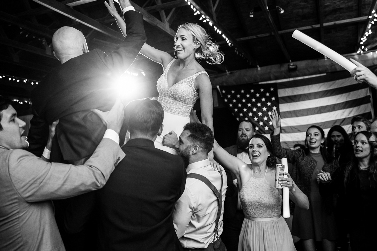 bride and groom lifted by wedding guests during reception song in black and white