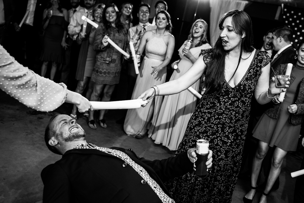wedding guests doing limbo during reception fun photographer black and white