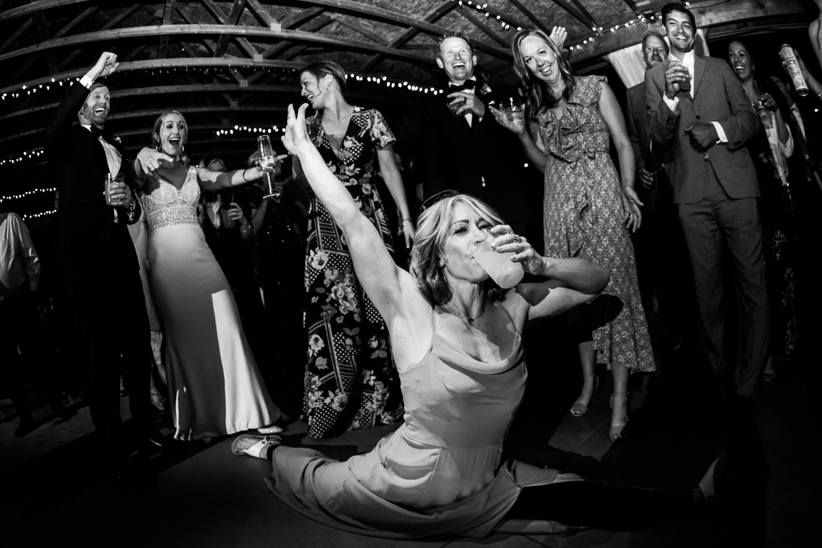bridesmaid doing splits while chugging beer during thunderstruck at wedding reception black and white wide angle