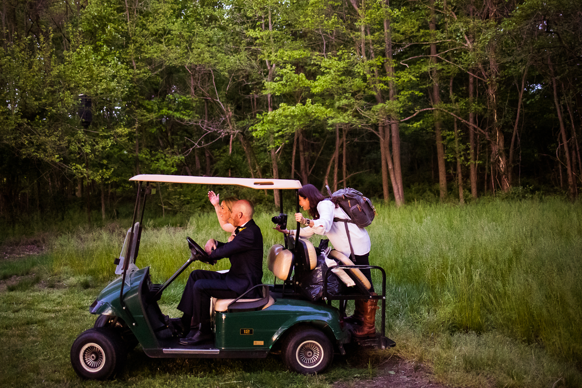 best creative photographer riding on the back of a golf cart taking the perfect shot of the newlyweds at camp wright
