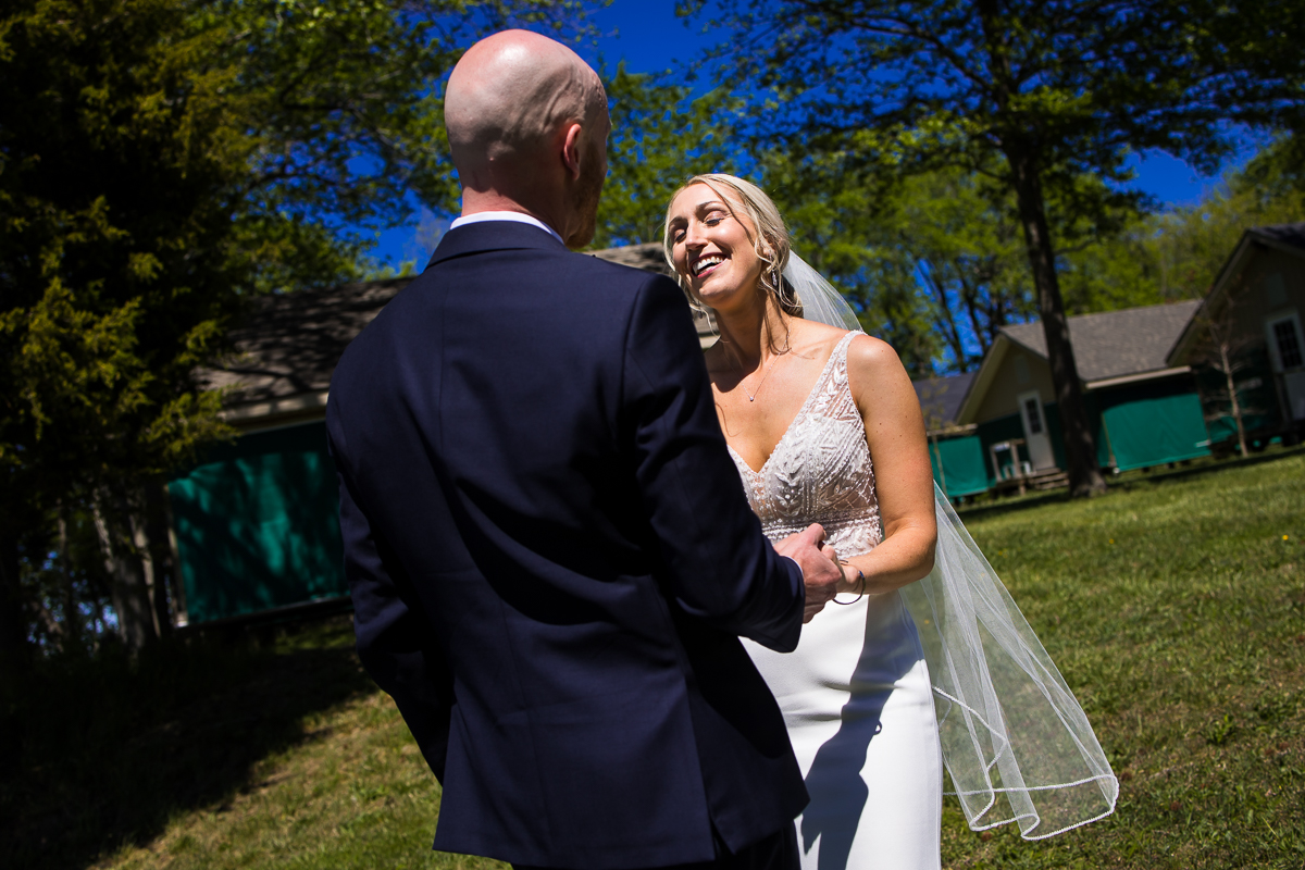 bride smiling during first look with groom outdoors at camp wright in Stevensville Maryland best photographer