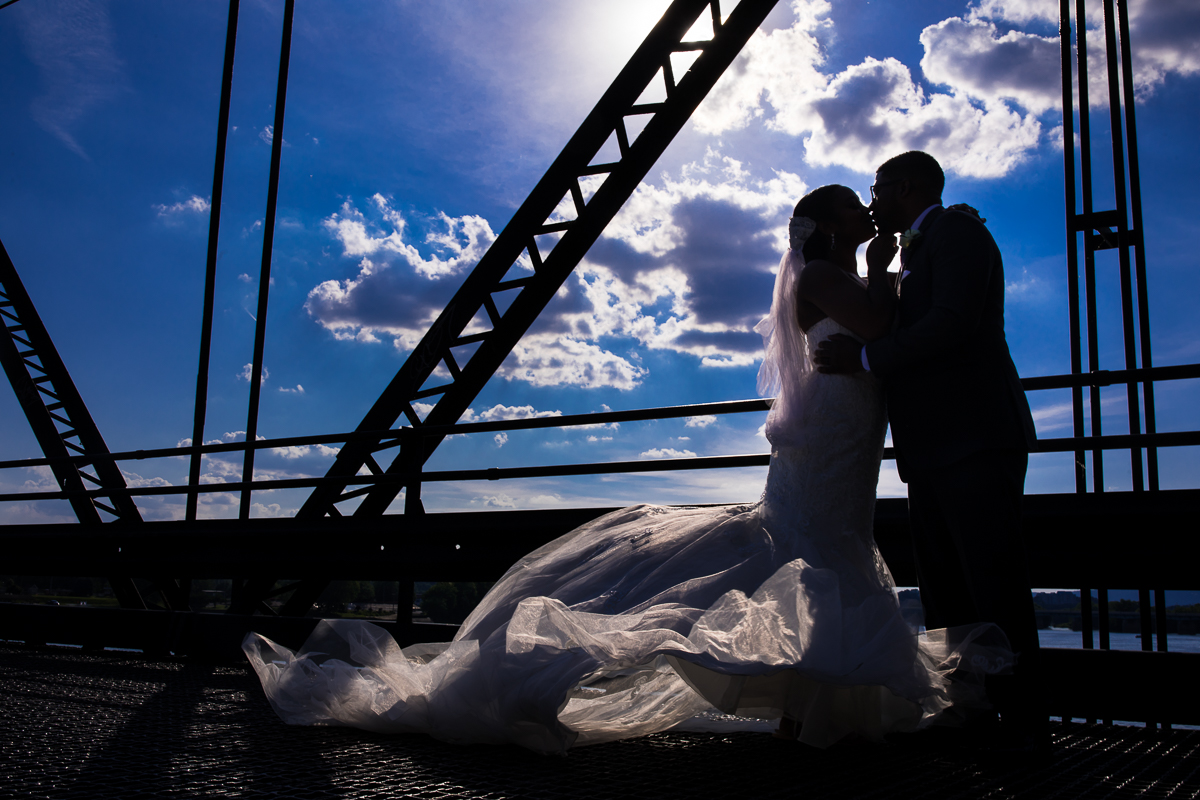 harrisburg capitol rotunda wedding central pennsylvania best wedding photographer creative artistic photo of bride and groom silhouetted in front of blue clouds on walnut street bridge