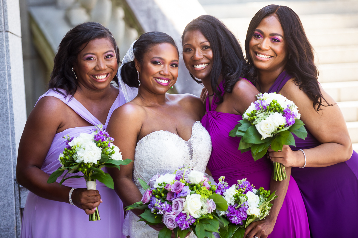 bride smiling with bridesmaids wearing shades of purple holding matching bouquet of purple green and white outside the Harrisburg capitol complex in pennsylvania