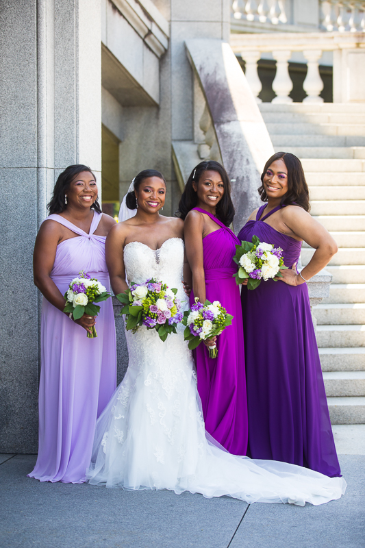 harrisburg capitol rotunda wedding bridesmaid portraits wearing purple dresses while smiling outside the steps in downtown Pennsylvania best award winning wedding photographer