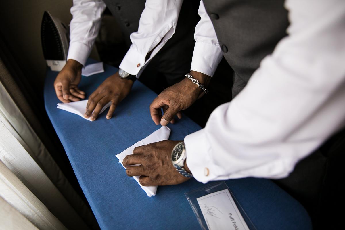 groom and groomsmen ironing pocket squares on Hilton Harrisburg hotel iron table folding details