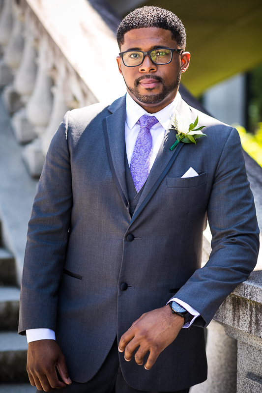 traditional groom portrait outside the Harrisburg capitol rotunda wedding ceremony steps groom wearing charcoal tux with purple tie and white rose
