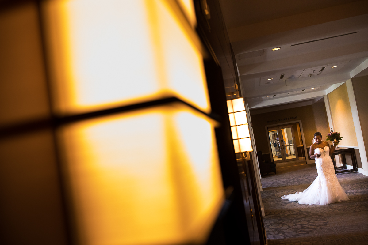bride walking down the hallway at Harrisburg Hilton before first look with groom wide angle creative shot fun artistic wedding photographer