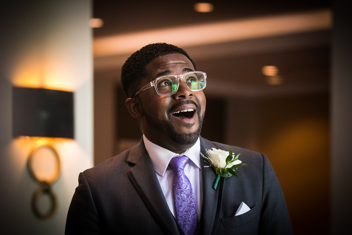 groom reaction to seeing bride for the first time on wedding day like looney tunes character with mouth gaping wearing gray tux and purple tie and clear glasses