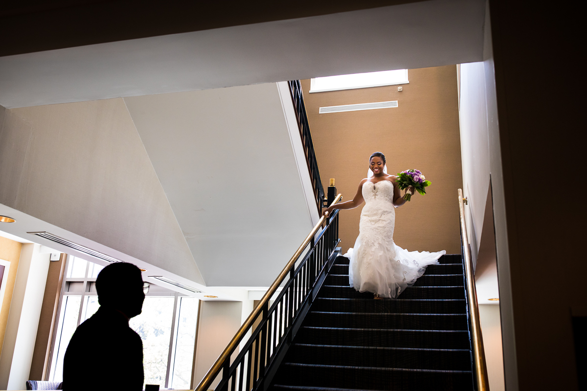 bride walking down the stairs to see groom for the first time on wedding day at Harrisburg Hilton creative unique fun wedding photographer central pa