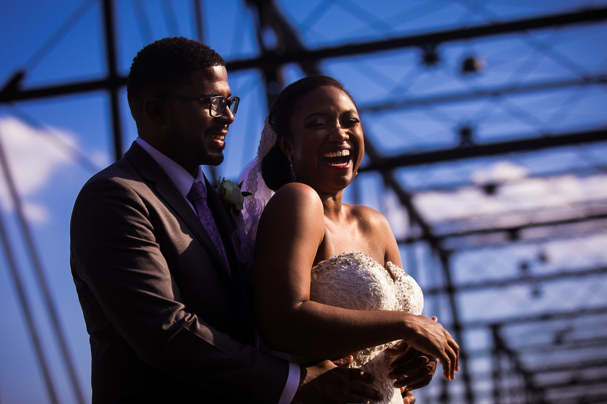 bride and groom smiling on walnut street bridge in downtown harrisburg with creative lines and elements best wedding photographer pa