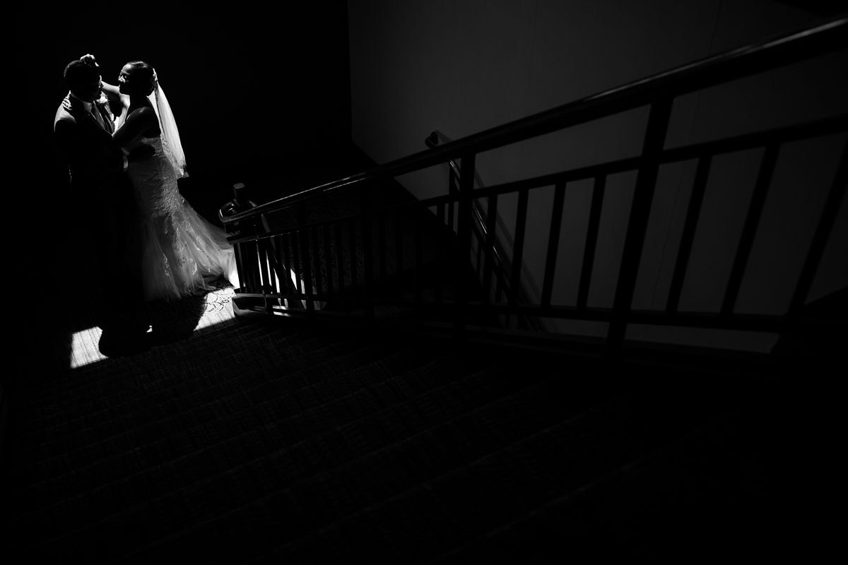 black and white artistic shot of light peaking through window shining on bride and groom dramatic contrast and lighting best award winning central pa photographer Harrisburg Hilton first look
