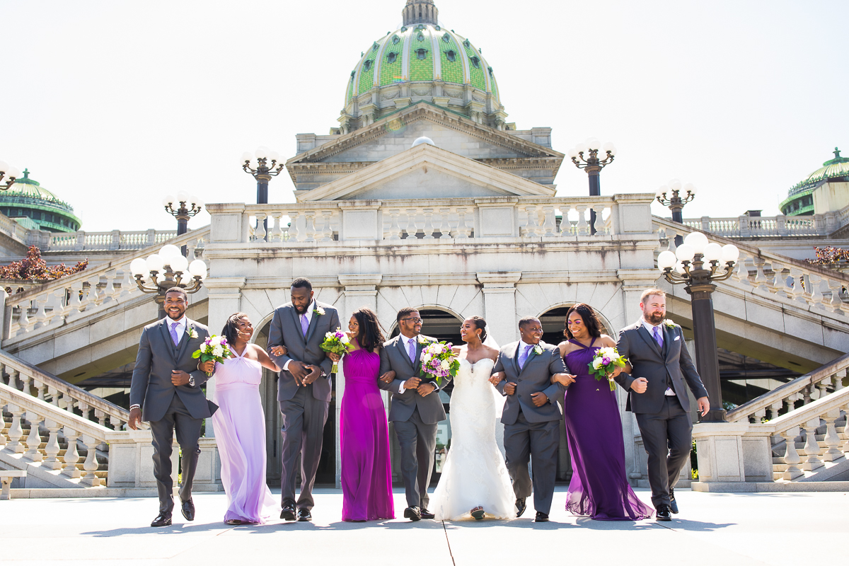 wedding party walking together linking arms in front of Harrisburg capitol rotunda wedding before ceremony downtown Harrisburg pennsylvania