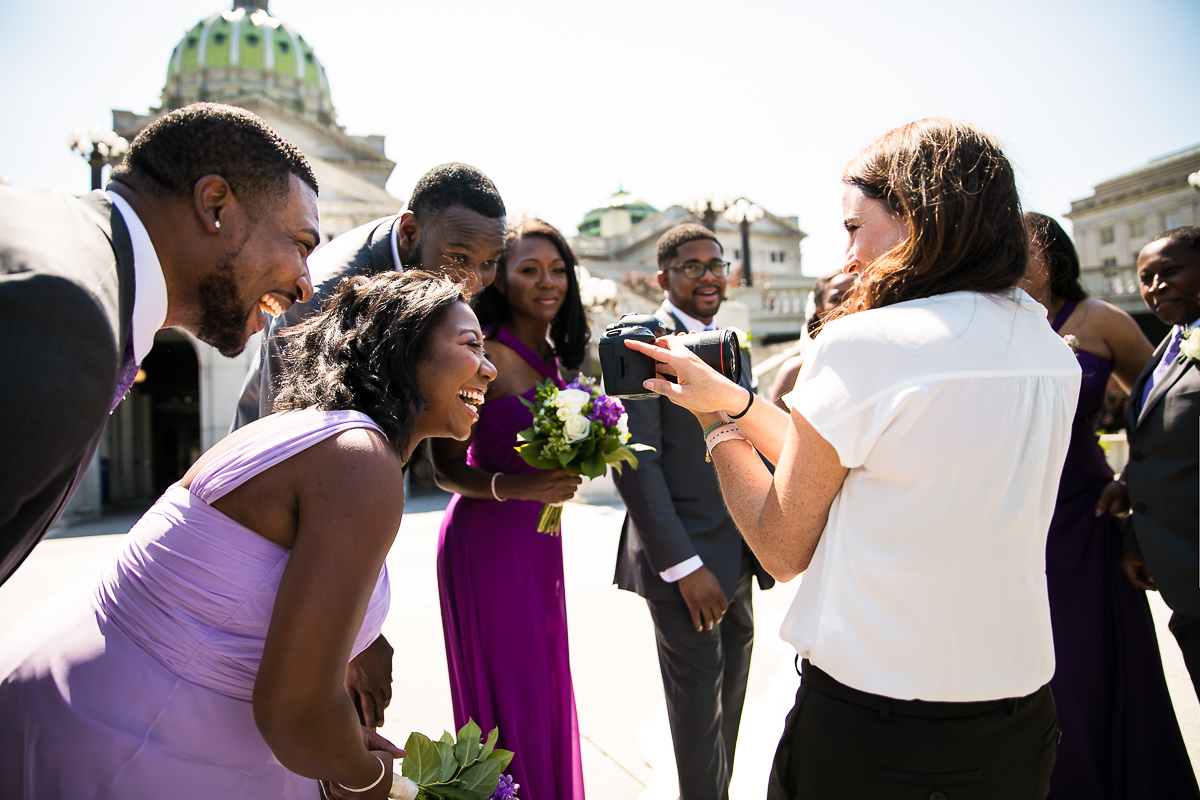 photographer behind the scenes showing wedding party photos on the back of her camera outside the Harrisburg capitol in downtown Harrisburg pa best award winning wedding photographer