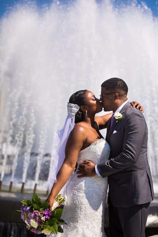 bride and groom portrait in front of fountain outside Harrisburg capitol rotunda wedding ceremony building with bride holding purple bouquet