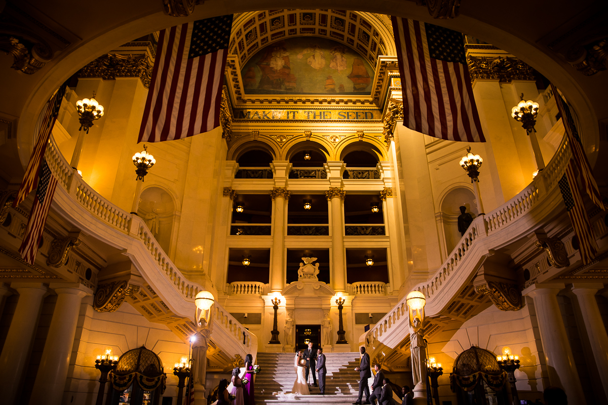 harrisburg-capitol-rotunda-wedding-photographer best award winning creative unique fun emotional candid make it the seed American flags hanging from banisters bride and groom standing on steps surrounding by family central pa wedding photographer