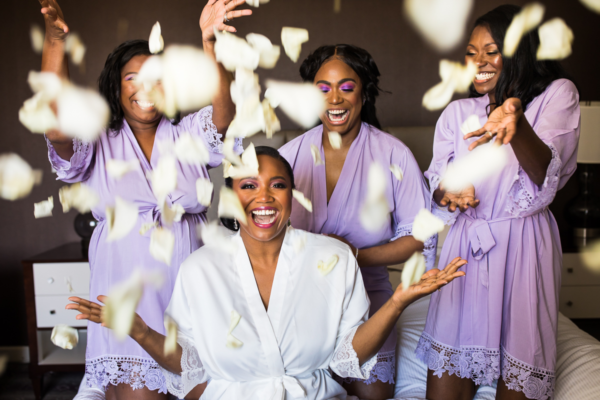 bride wearing white robe throwing confetti with bridesmaids wearing purple robes behind smiling and laughing at Hilton Harrisburg pennsylvania during getting ready fun artistic creative wedding photographer