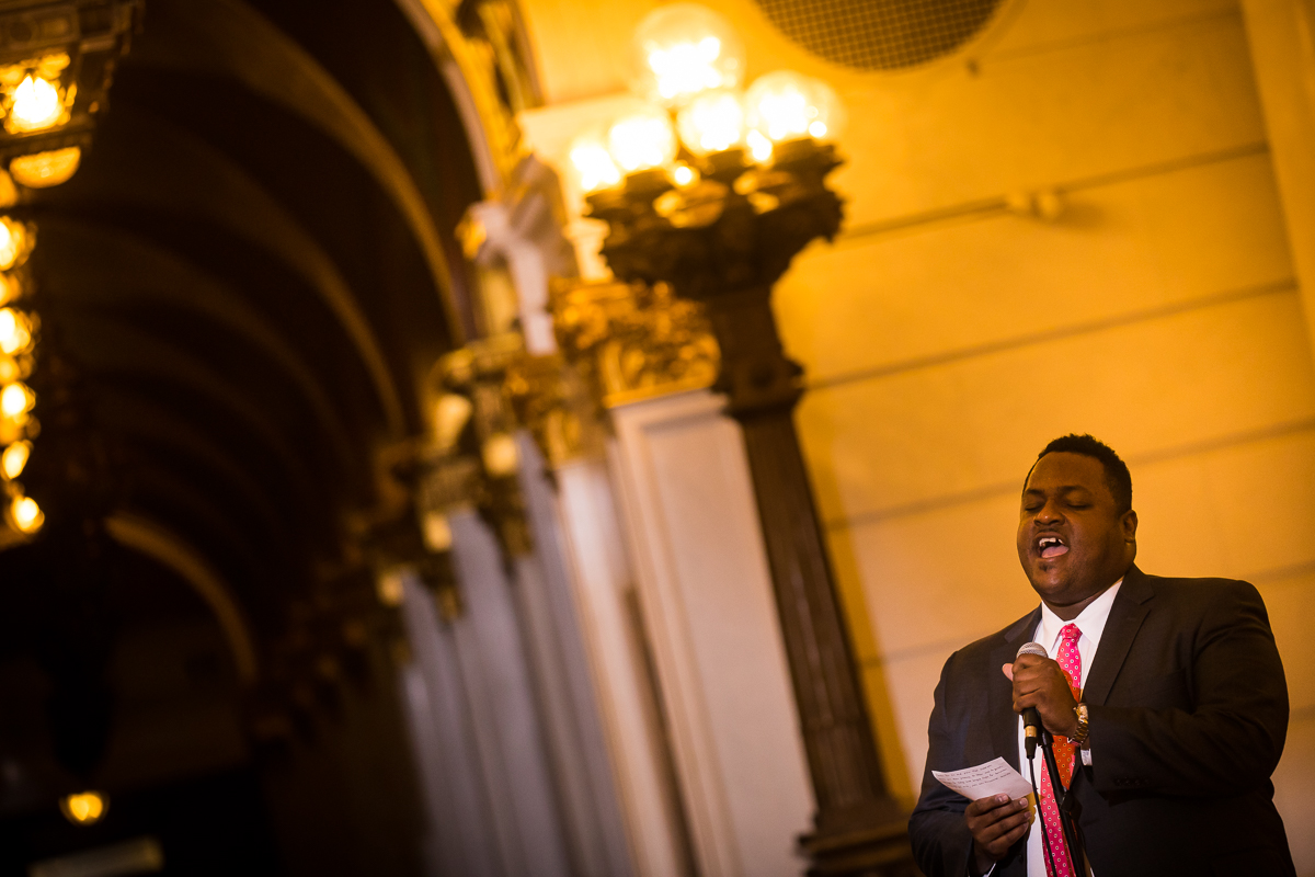man singing inside the Harrisburg capitol rotunda during wedding ceremony with architecture and unique lighting in background