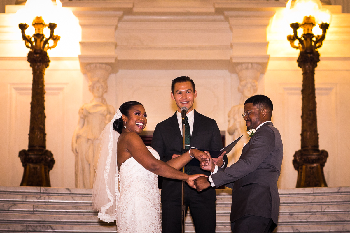 officiant during these hands ceremony during vows on Harrisburg capitol rotunda steps inside during wedding ceremony
