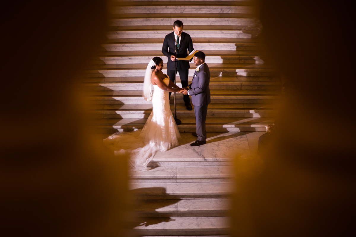harrisburg-capitol-rotunda-wedding-effortless creative beautiful vibrant unique creative artistic photographer bride and groom holding hands on steps with officiant during ceremony
