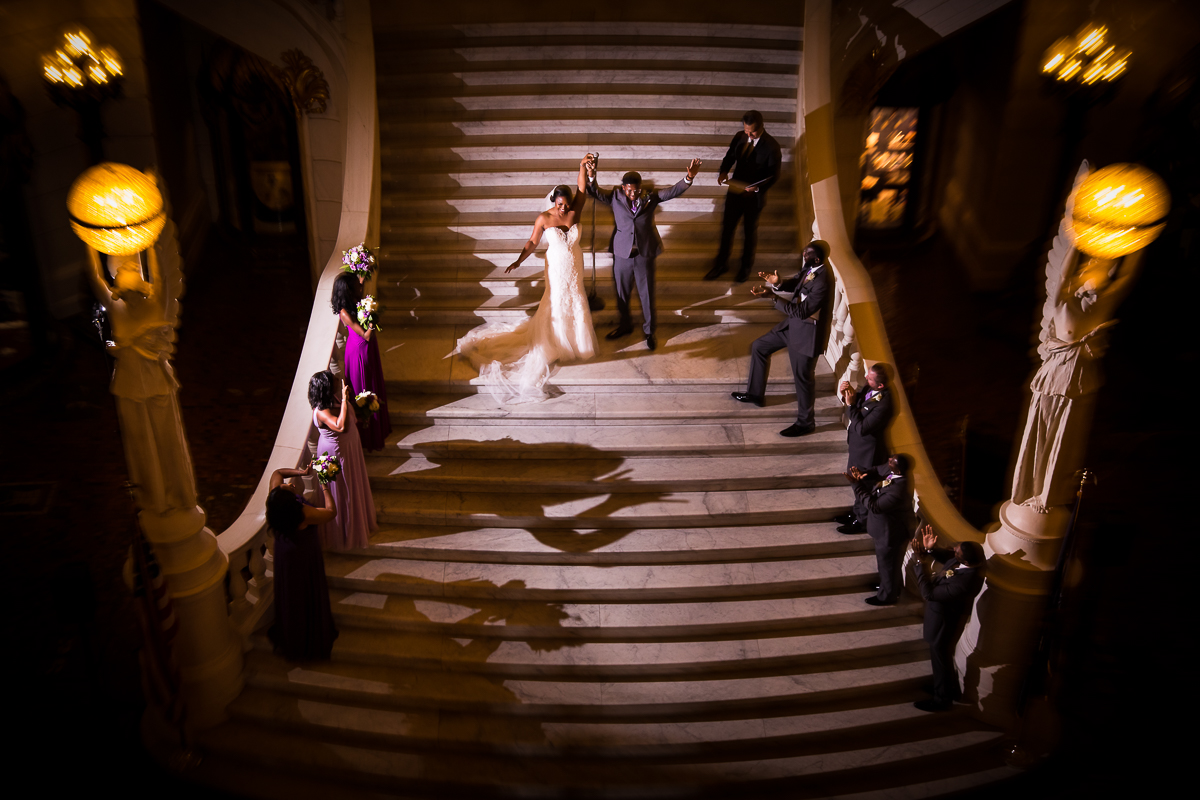 walking down the steps after becoming husband and wife at the Harrisburg capitol rotunda wedding ceremony with wedding party clapping and congratulating