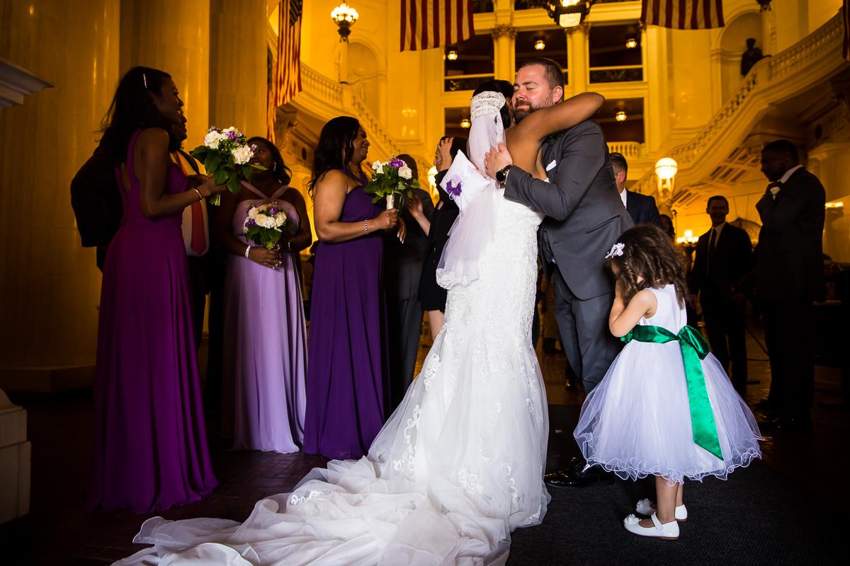 bride hugging wedding guest after ceremony emotional candid natural wedding photographer inside Harrisburg capitol rotunda wedding