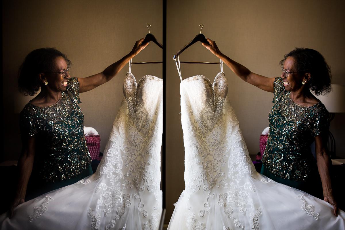 mom holding bride's dress in reflection creative artistic wedding photos award winning wedding photographer