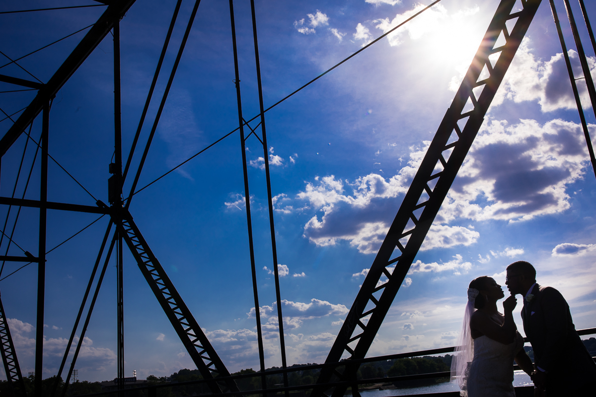 walnut street bridge downtown Harrisburg pa wedding photographer couple silhouetted with bridge architecture in background bright blue sky