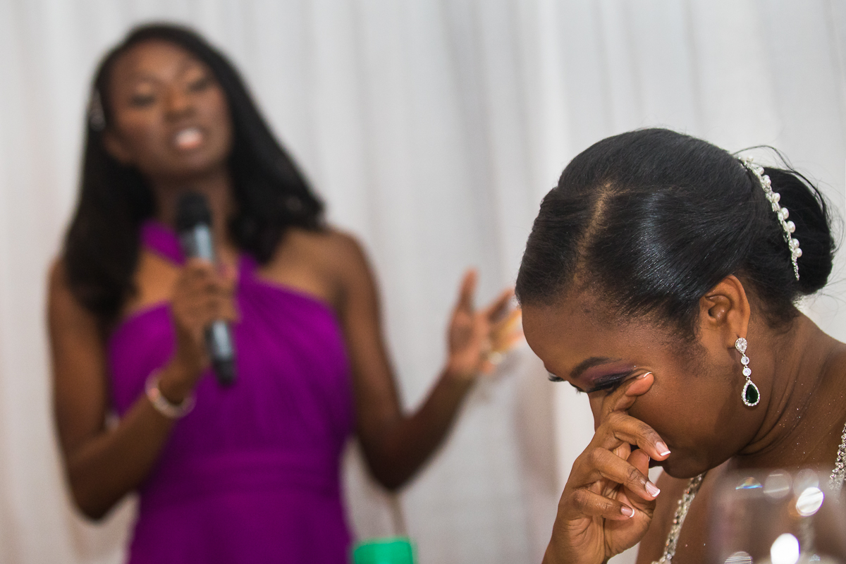 bride wiping tear away from face during sister's speech inside Hilton Harrisburg reception space best emotional pa wedding photographer