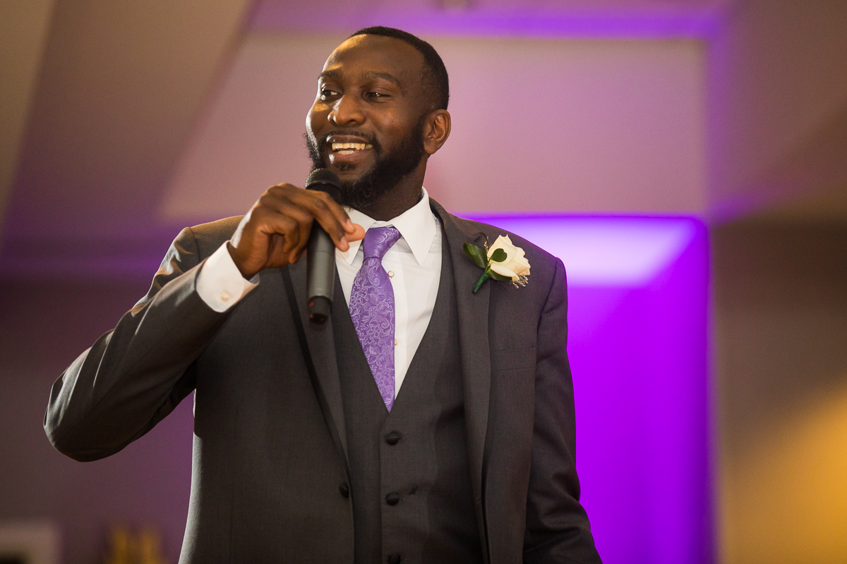 groomsmen smiling giving speech during wedding reception at Hilton Harrisburg pa with purple and white uplighting