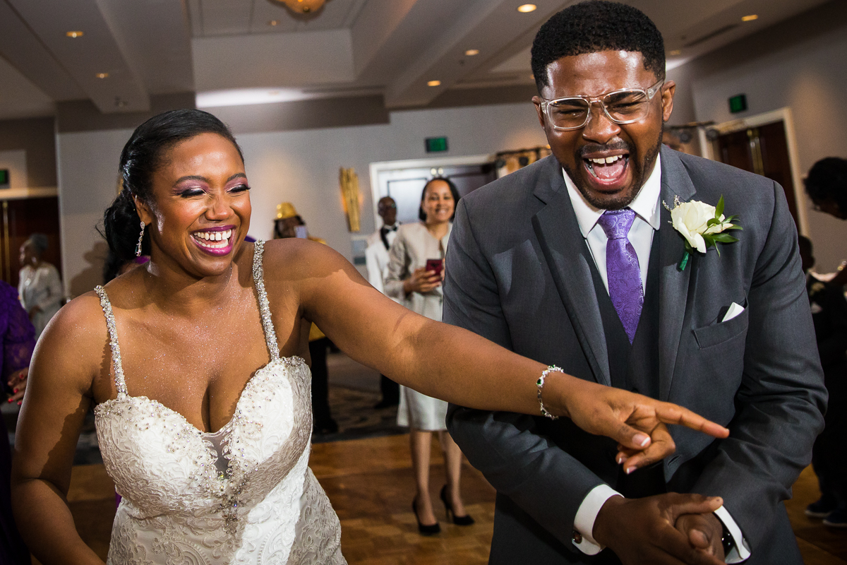 bride and groom smiling and laughing on the dance floor with guests surrounding them inside Hilton Harrisburg