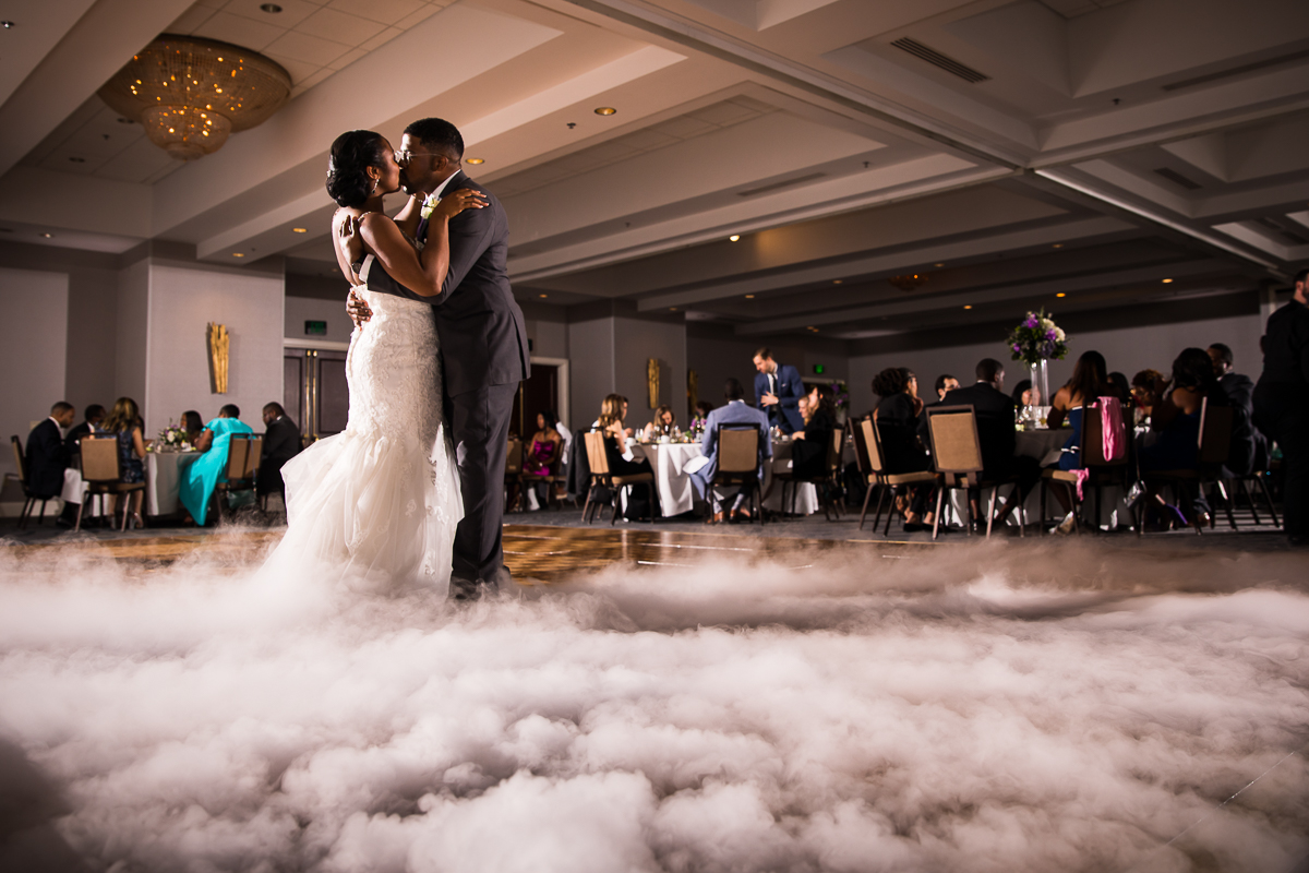 bride and groom share a kiss during first dance on a cloud inside Hilton Harrisburg reception space pa