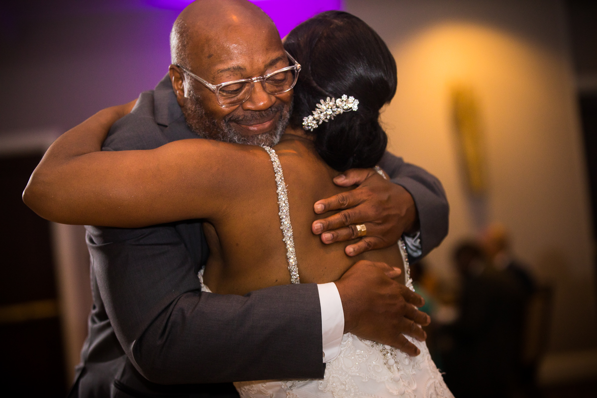 father hugging daughter after dance smiling inside Hilton Harrisburg pennsylvania wedding photographer
