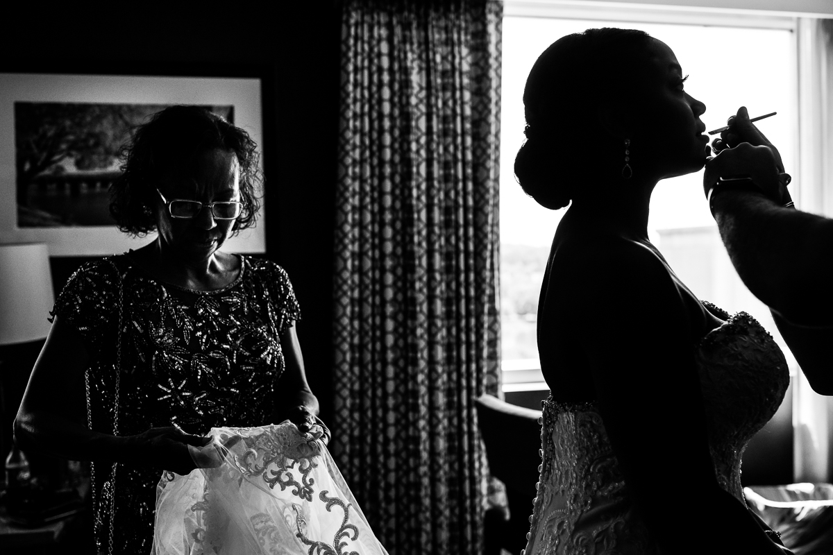 black and white photo of makeup artist putting lipstick on bride while mom admires detailing on bride's train of dress in hotel room getting ready at Hilton Harrisburg pa