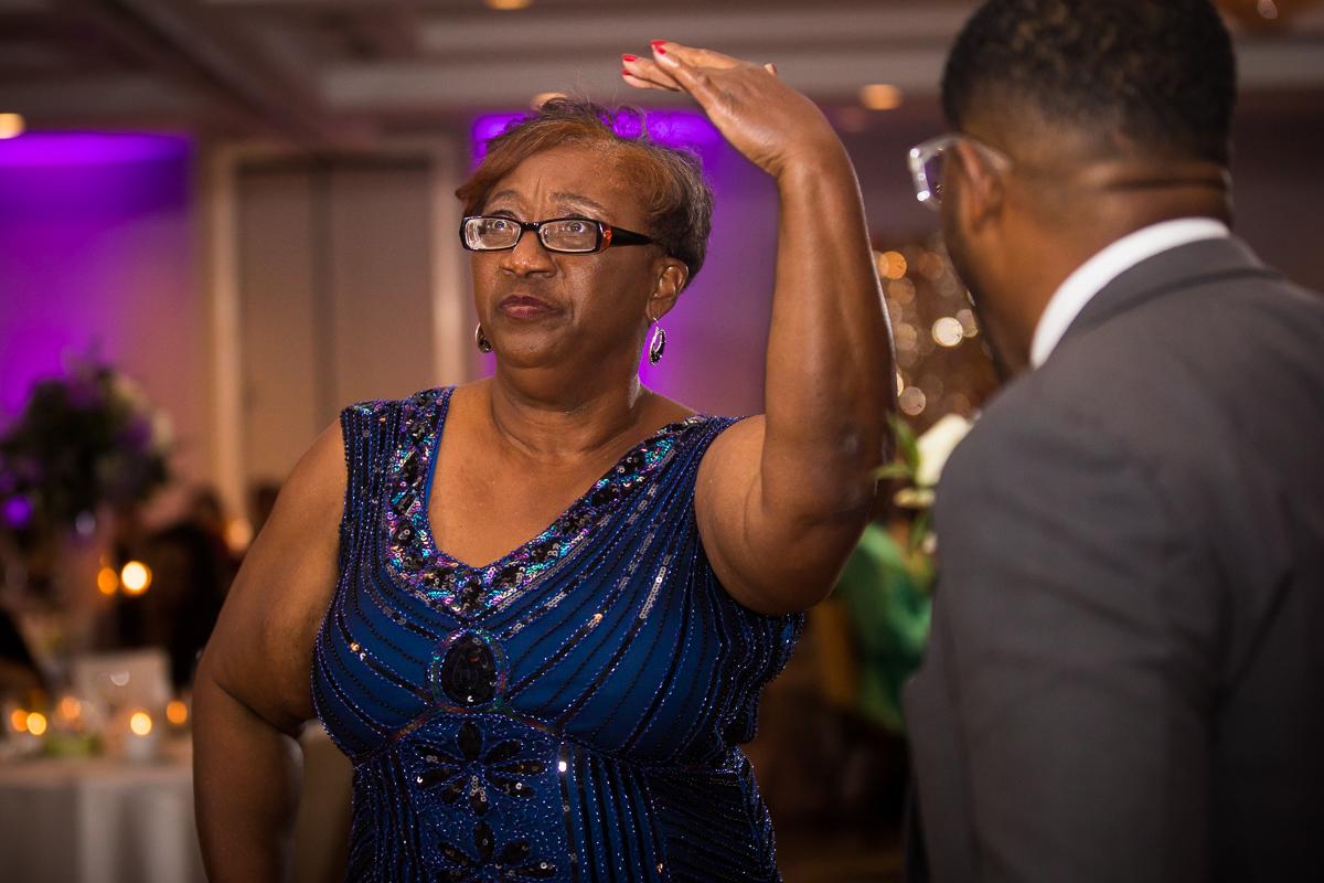 mother of groom dancing during reception inside Hilton Harrisburg pennsylvania fun candid wedding photographer