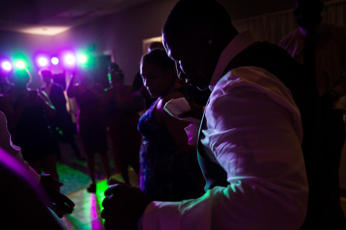 fun dj uplighting purple and green wedding guests dance and celebrate at Harrisburg Hilton