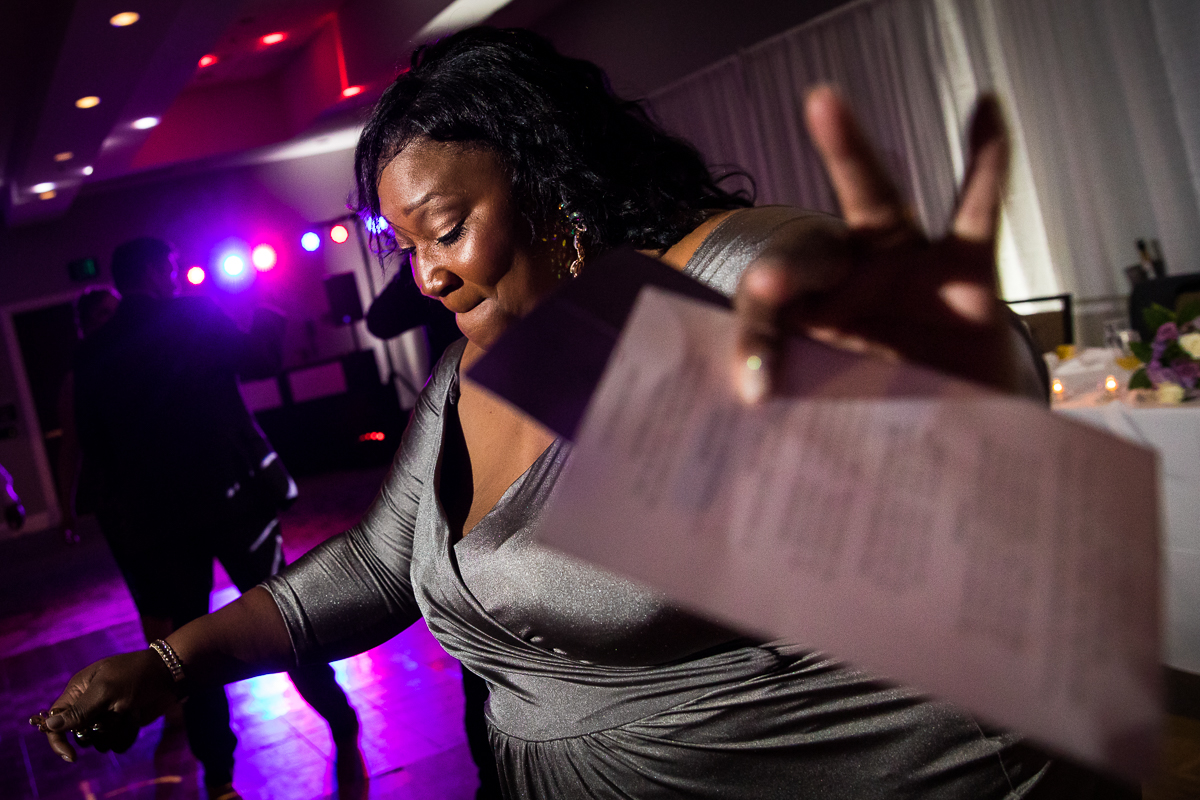 guest dancing at wedding reception wearing gray sparkly dress with lights in background on dance floor