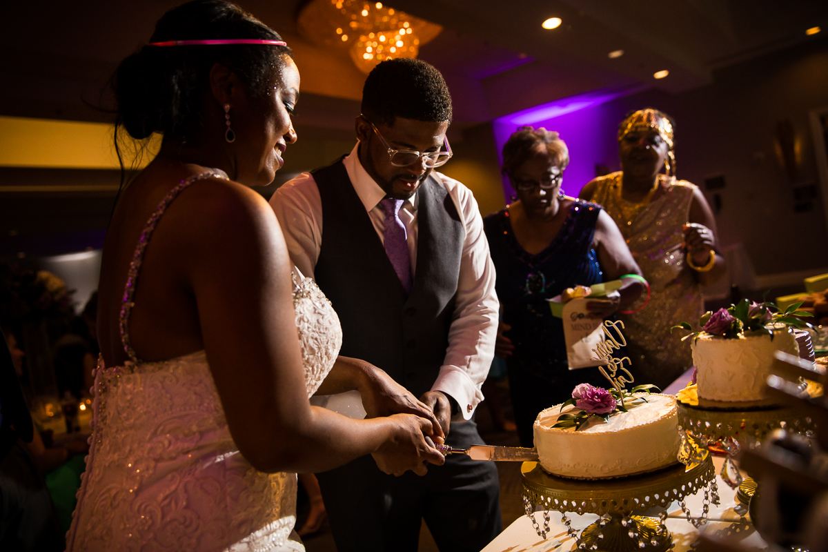 bride and groom cutting cake from Whole Foods during wedding reception deconstructed cake gold table Harrisburg Hilton