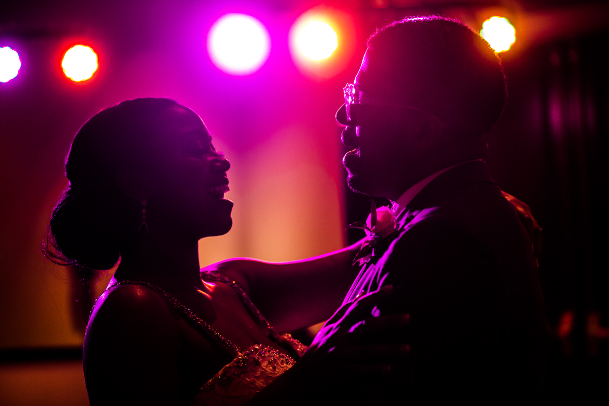 bride and groom smiling and singing to each other during dance during wedding reception purple lighting in background artistic photo award winning wedding photographer