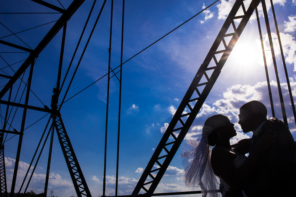 harrisburg-capitol-rotunda-wedding-walnut street bridge bride and groom photos silhouetted against blue sky with unique architecture