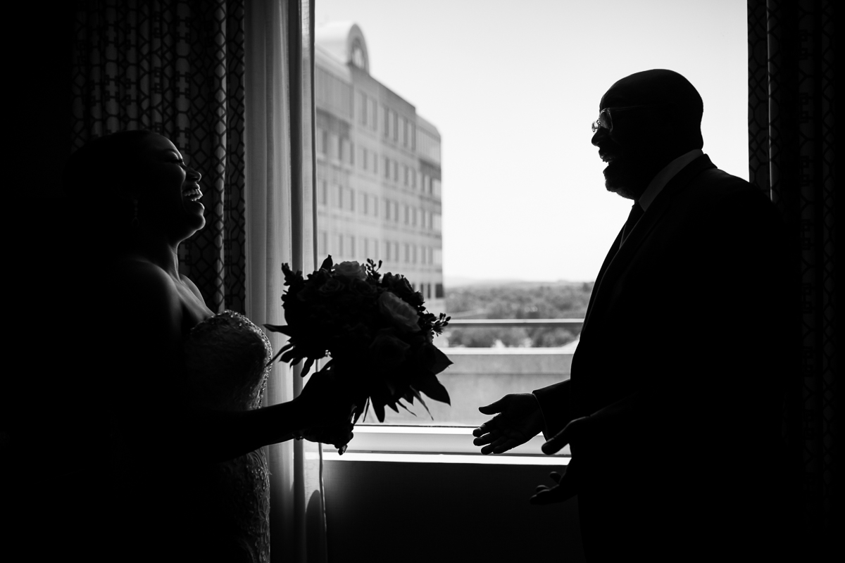 black and white emotional photo of first look between father and daughter in front of window with downtown harrisburg in distance