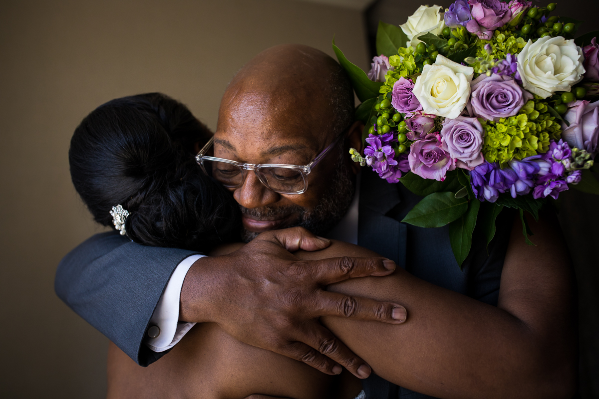 father of bride hugging bride on wedding day while she holds purple white and green rose bouquet during first look at Hilton Harrisburg downtown pa