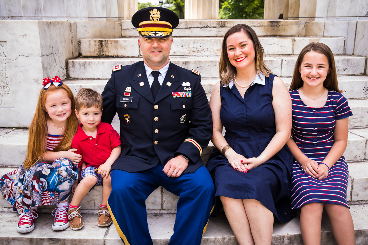 family sitting on steps smiling after dc military promotion ceremony dressed in patriotic colors DC family photographer military promotion photographer