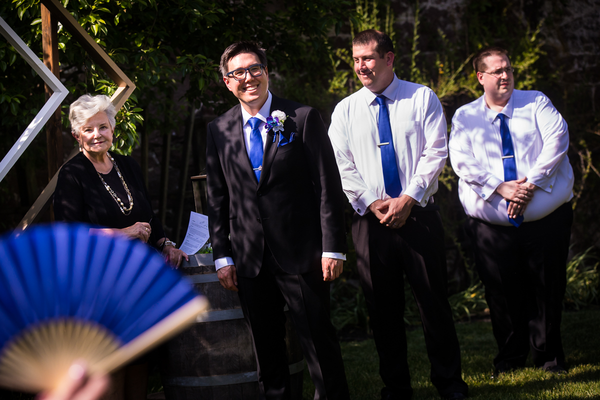 officiant groom and groomsmen standing at altar wearing blue ties with blue fan overlay waiting for bride
